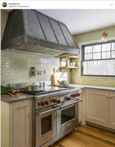 Wall mount artisan cast zinc range hood with a slant front design against light green tiles.