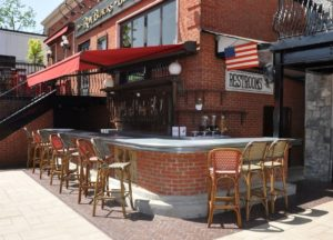 Curved zinc bar top installed in an outdoor bar with brick bar front and a red awning.
